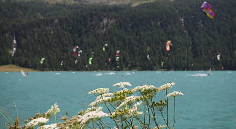 Kitesurfing on the lake in the mountain landscape of Engadin